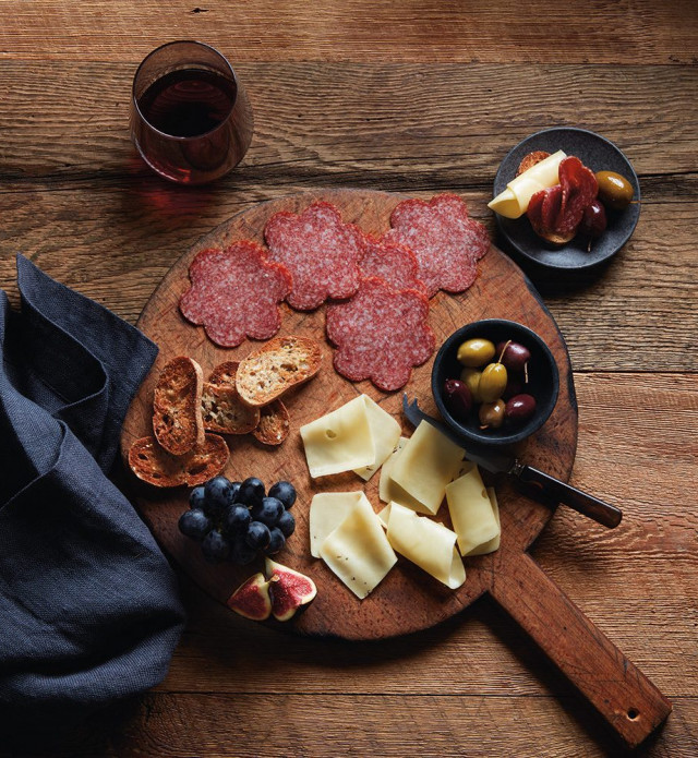 flower shaped sliced meat with cheese and figs on a board
